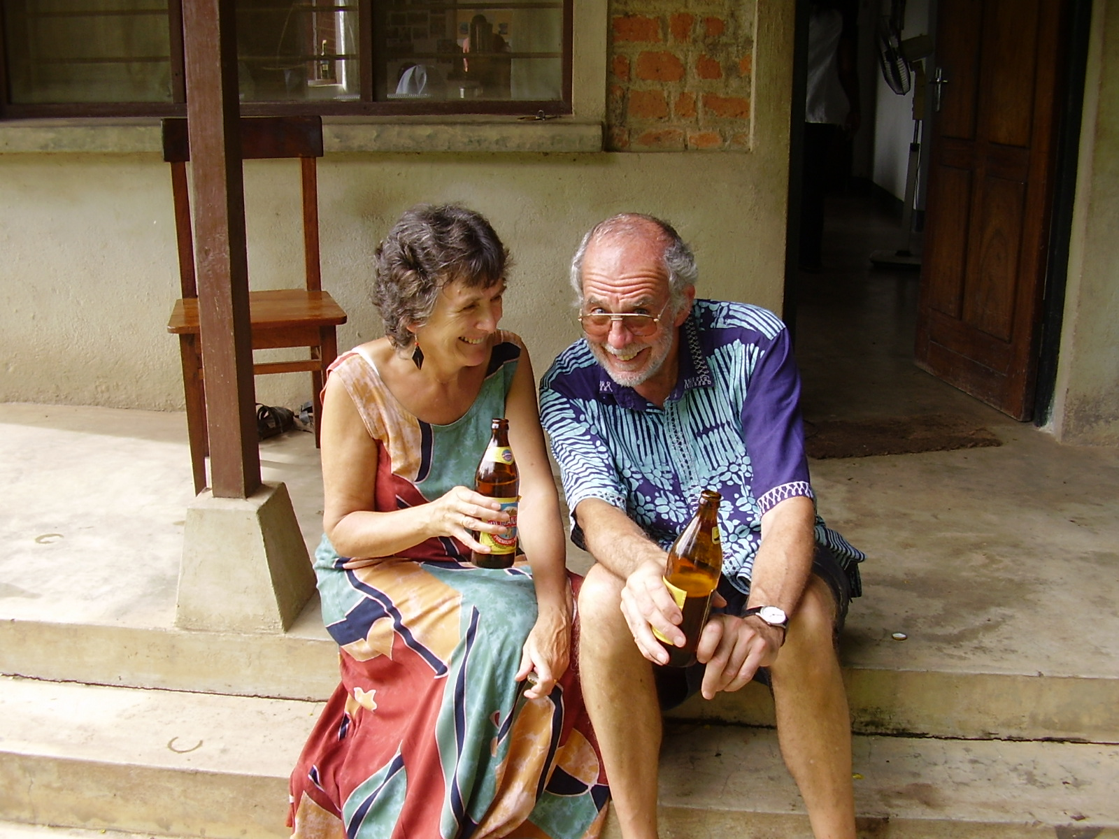 Man and woman holding a beer and laughing